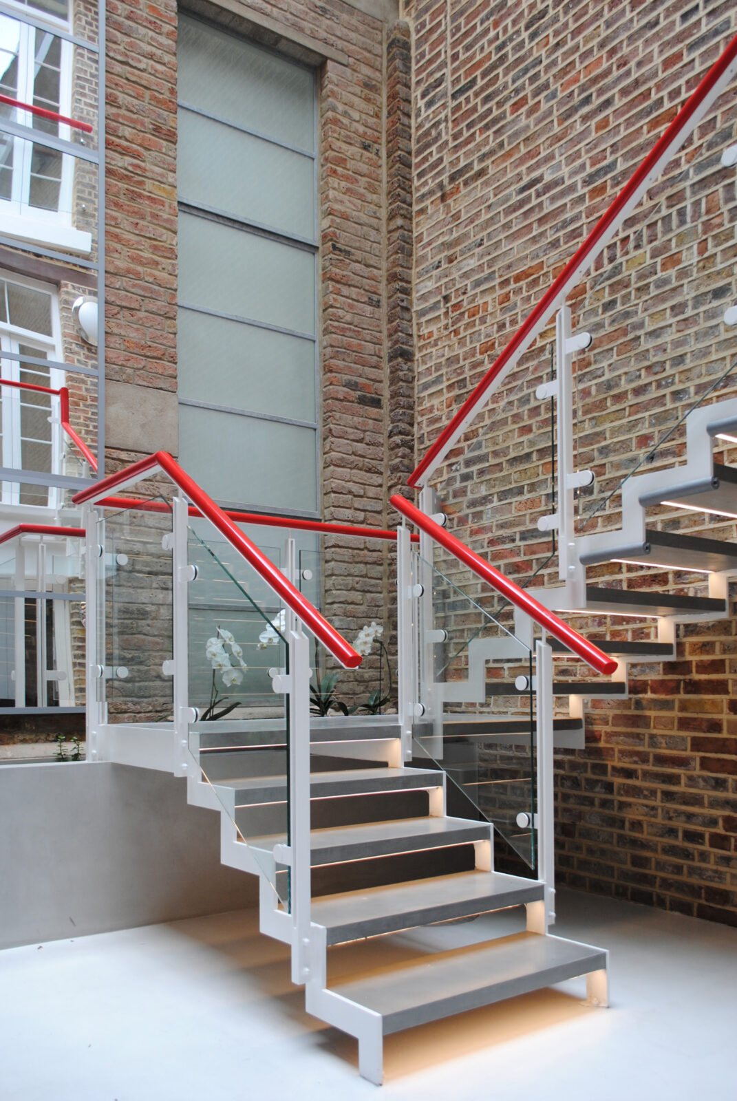 Photo of contemporary open tread steel and glass stair